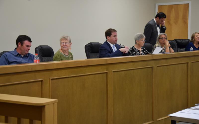 Franklin County Board of Elections and Registration members (from left) Roman Strickland, Alice Black, Chairman Doug Kidd, Sherry MacDonald and Angela Whidby (with County Attorney Bubba Samuels and Elections Superintendent Gina Kesler) prepare to listen to tesimony following a break in a hearing Wednesday on a challenge to the residency of Lee and Sheena Strickland.