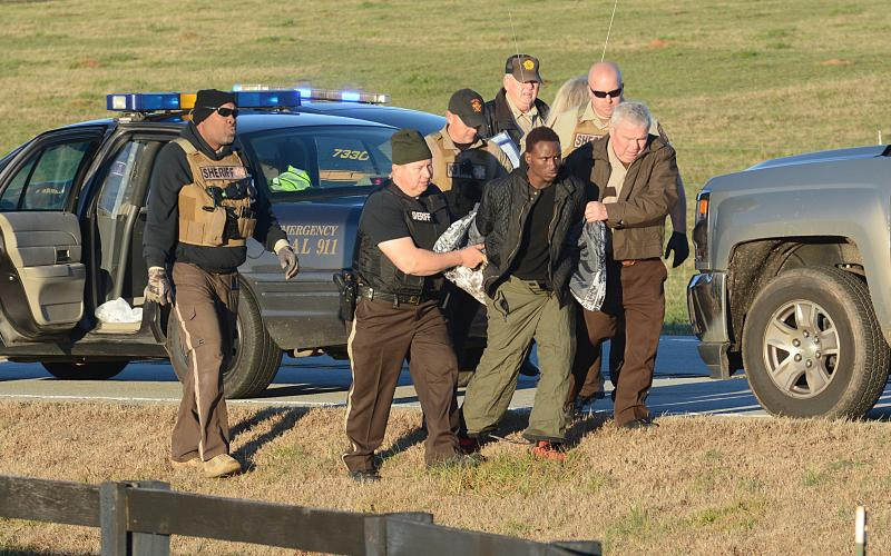 Hart County Sheriff's deputy David Cleveland (left) and Sheriff Mike Cleveland (right) escort murder suspect Larrendrick Rashad Tabor after his arrest Tuesday near South Hart Elementary School in Hart County. (Photo courtesy of The Hartwell Sun)