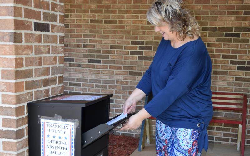 Franklin County Elections Supervisor Gina Kesler demonstrates how to drop off an absentee ballot at her office's new outside drop box that will be available for the June 9 primary.