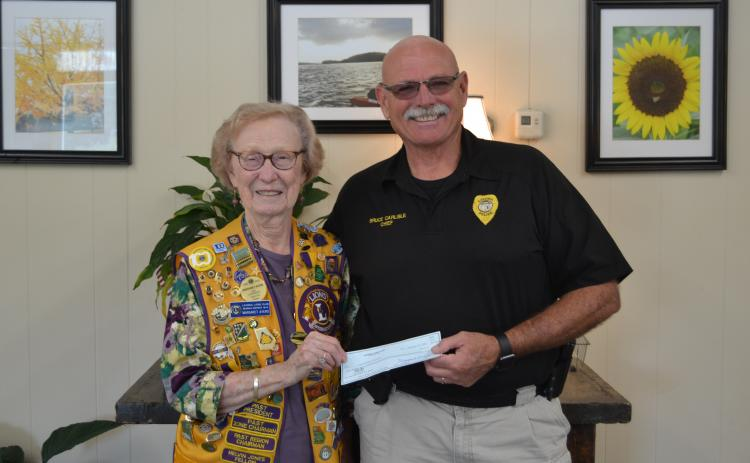 The Lavonia Lions Club, in conjunction with the Lavonia Police Department, will sponsor National Night Out  today beginning at 5 p.m. in downtown Lavonia. Pictured is Lavonia Lions Club member Margaret Ayers presenting Lavonia Police Chief Bruce Carlisle with a check for the event. (Photo by Eberhardt)