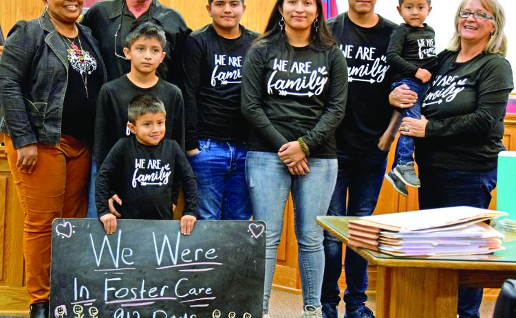 Steve and Angela Whidby completed the adoption Thursday of six siblings who had been in foster care with the family since 2017. Pictured in the courtroom at the Franklin County Courthouse are (front) Angel (holding sign) Felipe, (back) Case Manager Stephanie Tate, Steve Whidby, Edwin, Jennifer, Jose, Emmanuel and Angela Whidby. It was the largest single adoption in county history. (Photo by Scoggins)