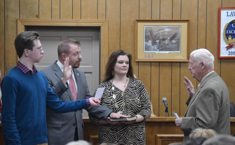 New Lavonia Mayor Courtney Umbehant (center on left), surrounded by son Noah and wife Natalie, takes the oath of office from outgoing Mayor Ralph Owens Monday during the Lavonia City Council's first meeting of 2020. (Photo by Eberhardt)