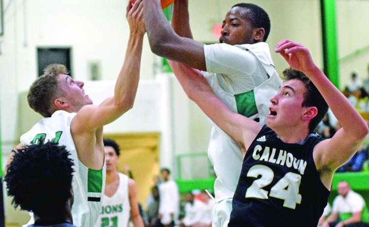 Lions Carter Alexander and JoJo Hughes (above) battle for a rebound against Calhoun Saturday in the Lions Den.