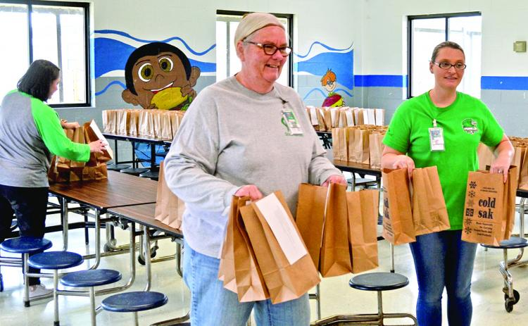 Members of the Franklin County School System's nutrition department tote lunches after a program began in March to provide meals to students in the community. By the time the program ended June 23, the system served more than 200,000 meals.
