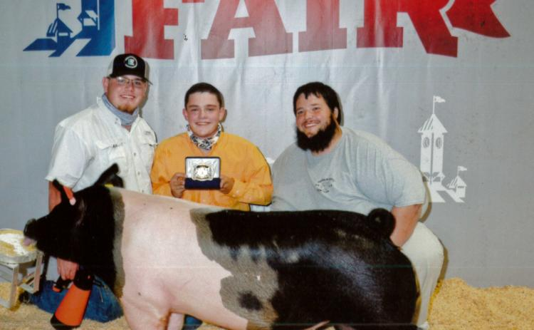 Devin Bowyer (center, with FCHS ag teacher Trey Harris at right) is one of the students who has benefited from being able to leave his pig project at the ag barn at Franklin County High School. Bowyer, one of the barn's student managers, began showing pigs two years ago and won Senior Showmanship recently at the Georgia National Fair. A new ag barn that will allow more students to keep their pigs, sheep, goats and calves at school will be funded if voters choose to extend a special purpose local option sale